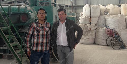 take photo with customer in front of the briquette machine in fluorite briquette plant