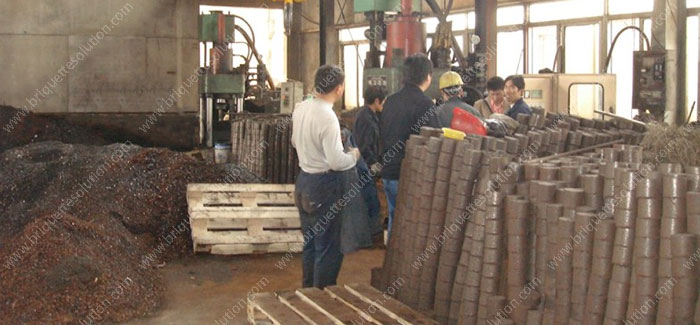 hydraulic briquetting machine press iron ore in a metal waste recycle factory and some people is checking the machine
