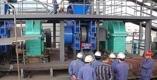 a hydraulic roller briquette press machine is briquetting mineral powder with workers around